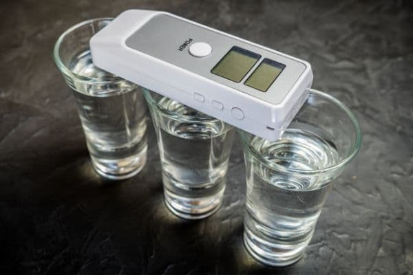 A breathalyzer laying across several glasses in alcohol