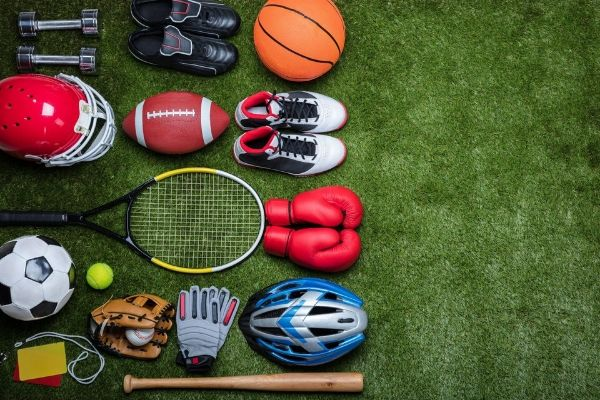 A large assortment of sports gear and acessories laying against a football field.